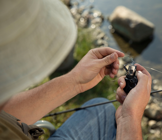 Fisherman using the Mag-Torch MT16 Pocket Torch to burn fishing line