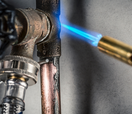 Flame from a Mag-Torch MT200C torch being used to heat up a metal pipe