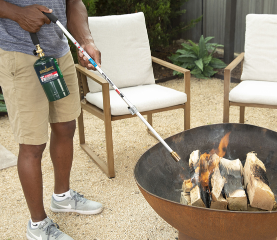 Mag-Torch MT450C Outdoor Torch being used by person to light fire pit wood