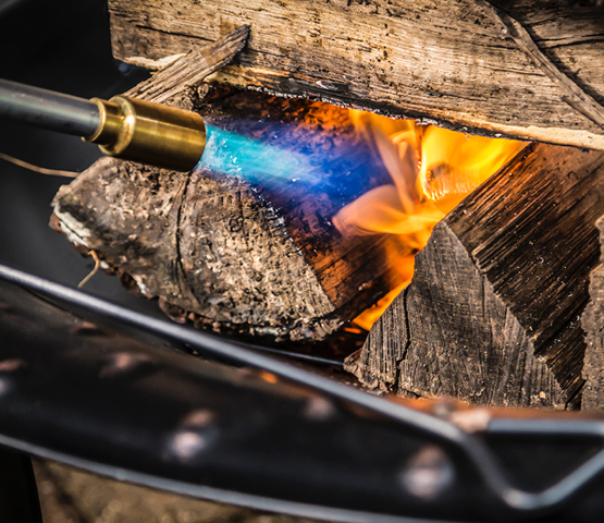 Mag-Torch MT450C Outdoor Torch being used to light a pile of wood on fire