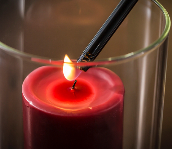 MT750 lighter being used to light a red candle in glass vase