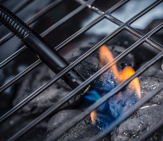 Using a lighter to ignite coals in a grill